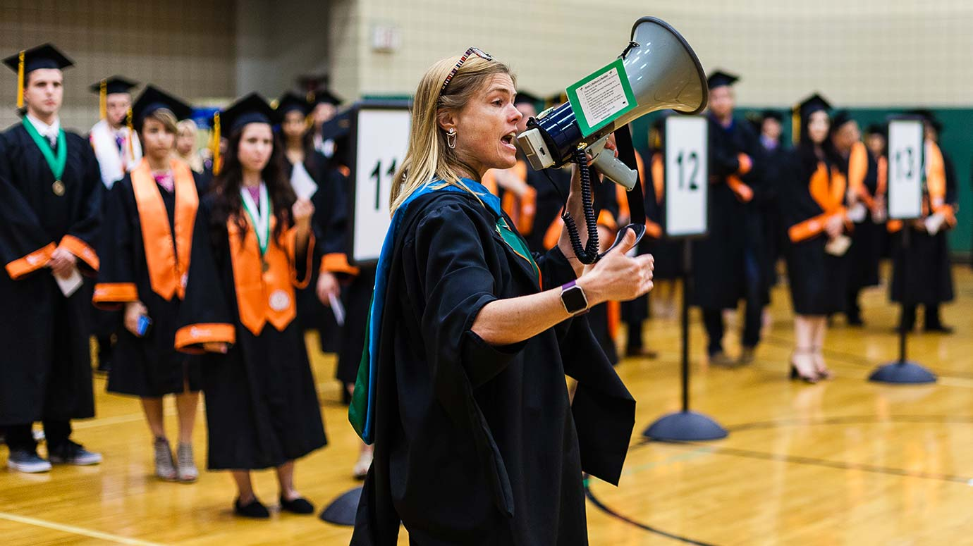 University Registrar Jennifer McDowell gives instructions about the procession to students from the School of Behavioral and Brain Sciences before their commencement ceremony